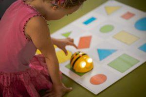Ein 5 Jahre altes Mädchen navigiert eine BeeBot Biene durch eine bunte Unterlage