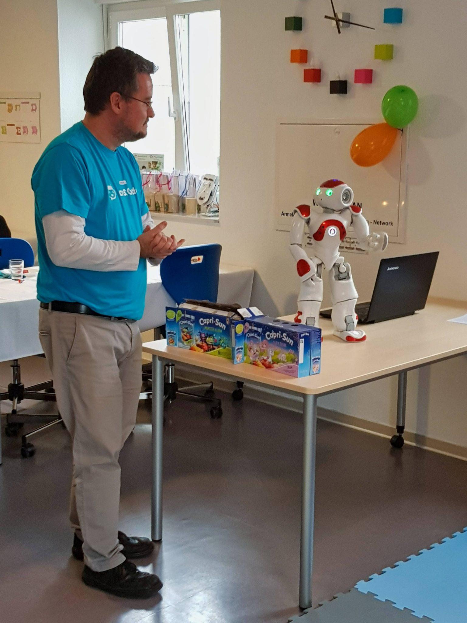 Kursleiter Patrick zeigt den Kindern den humanoiden Roboter Nao bei einem Kindergeburtstag