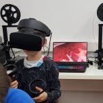 Ein Junge hat VR-Brille und steht vor einem Computer