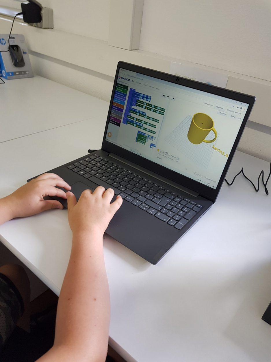 Ein Kind erstellt eine 3D gelbe Tasse in einem Programm