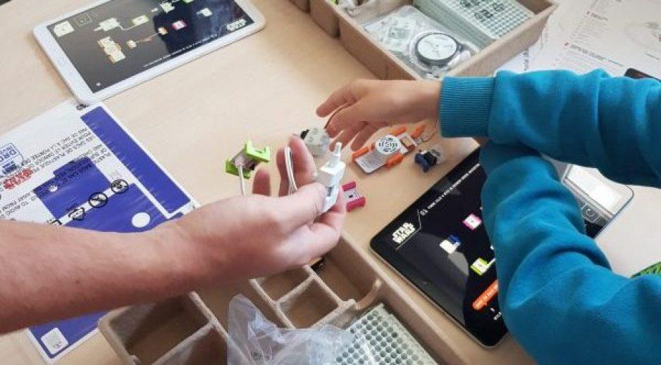 Bild auf dem man Kinderhände sieht und verschiedene kleine Bauteile, aus denen die Kinder Roboter bauen