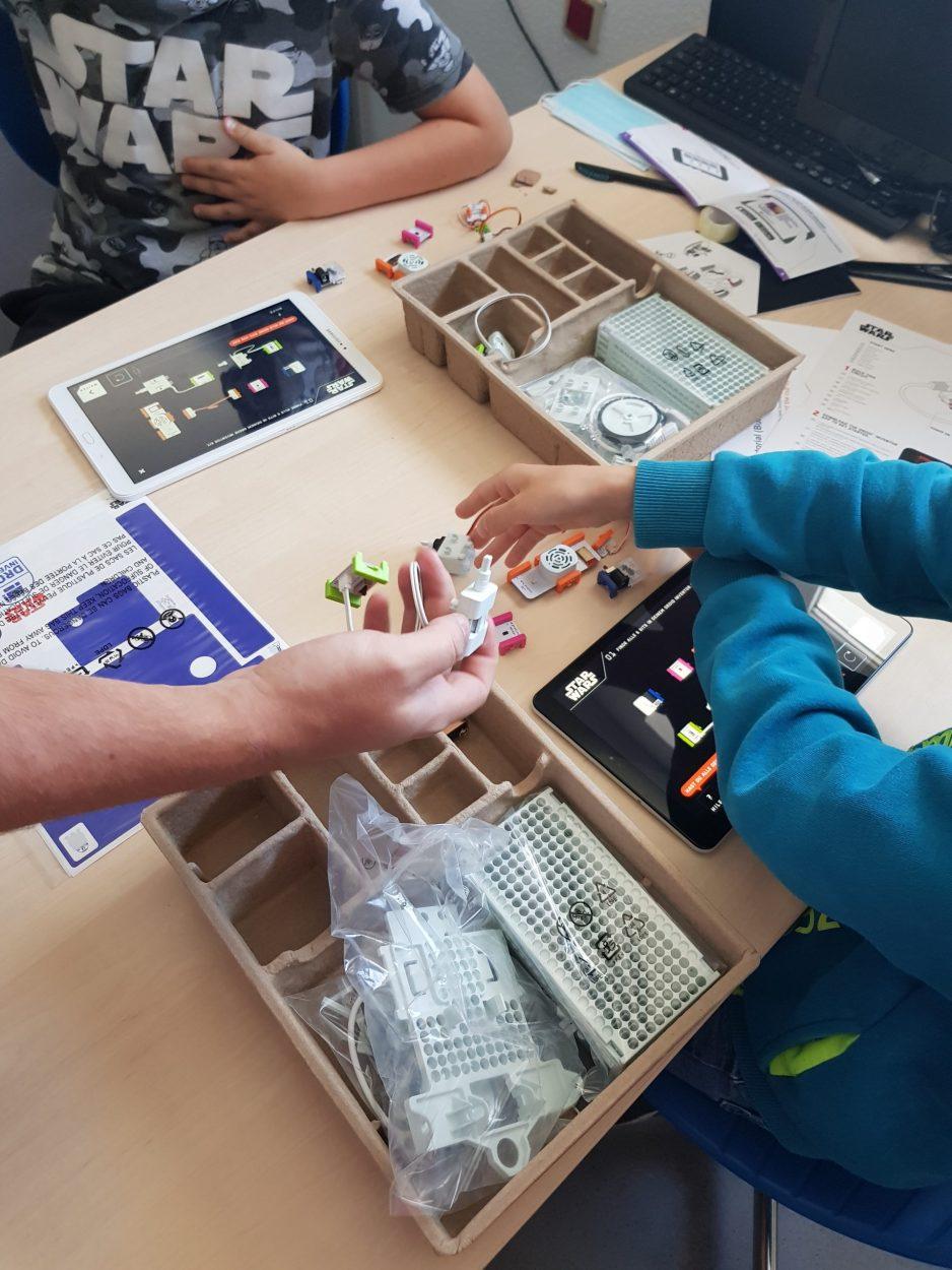 Kinder bauen aus verschiedenen Bauteilen kleine Roboter