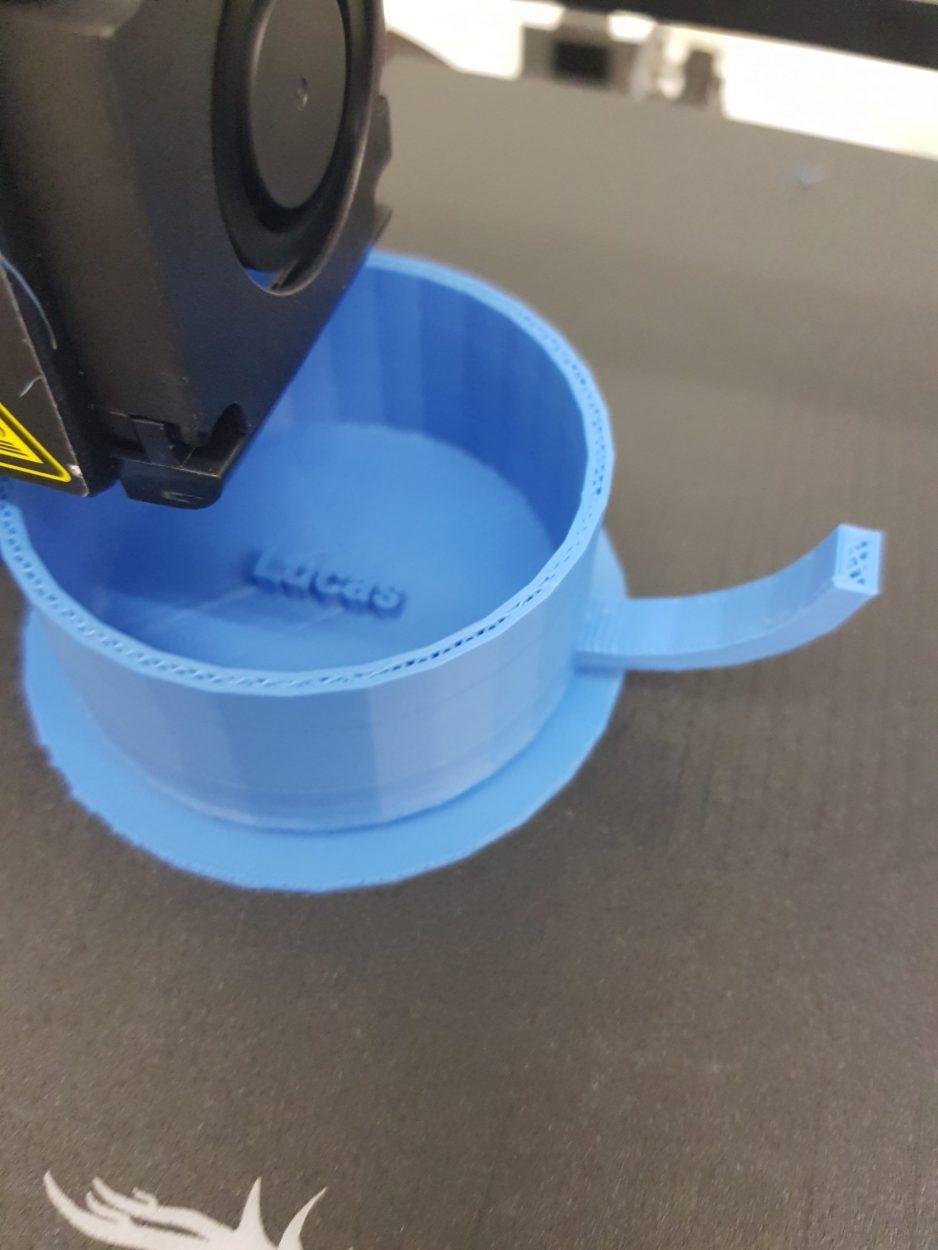 Das Bild zeigt wie ein 3D Drucker eine Tasse mit einem Namen druckt