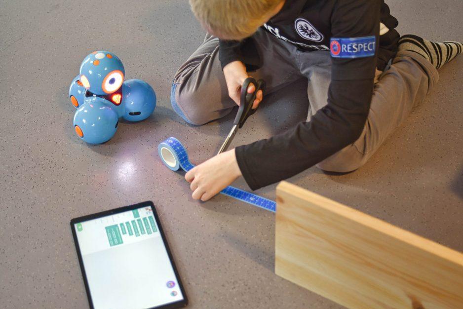 Ein Junge schneidet eine Massband für einen Labyrinth, durch den er den Dash Roboter fahren lässt.