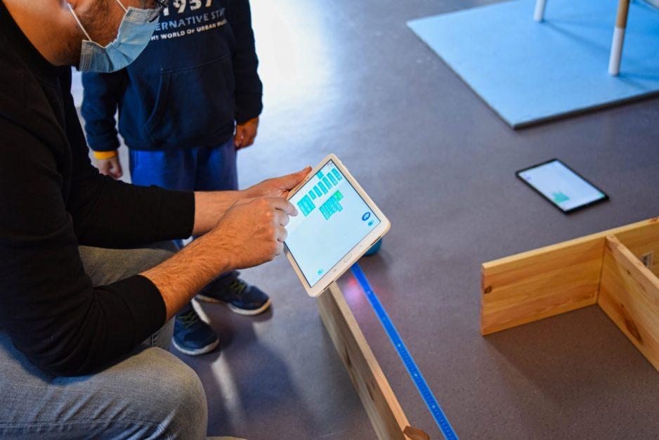Kursleiter hilft einem Jungen beim Programmieren auf dem Tablet