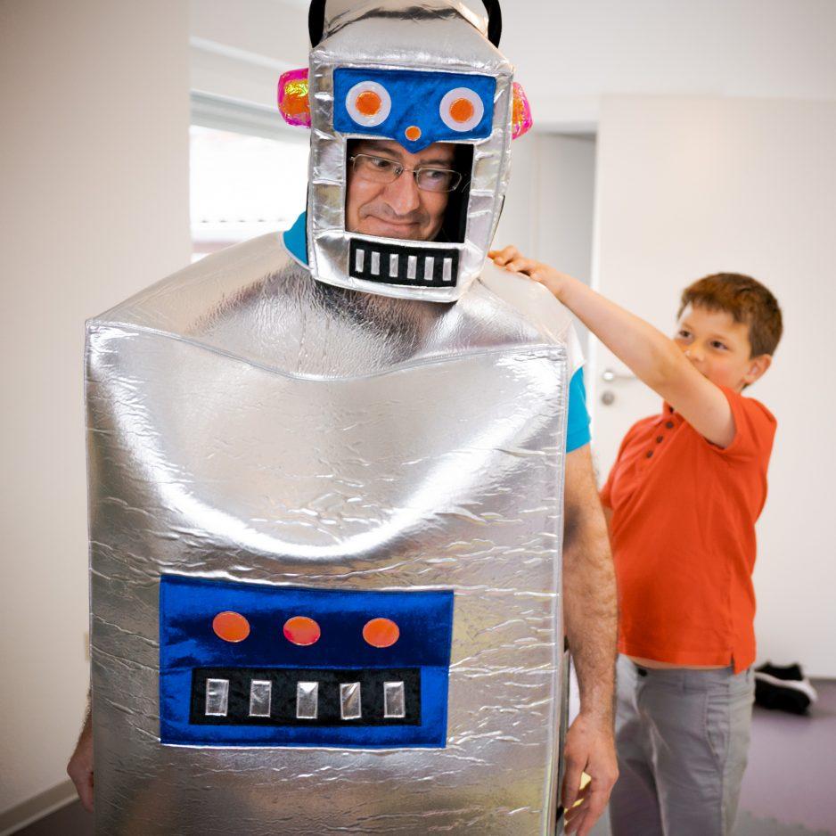 Roboter Kinderspiel - ein Kind versucht einen Roboter durch den Raum zu navigieren. Der Roboter ist ein umgekleideter Kursleiter