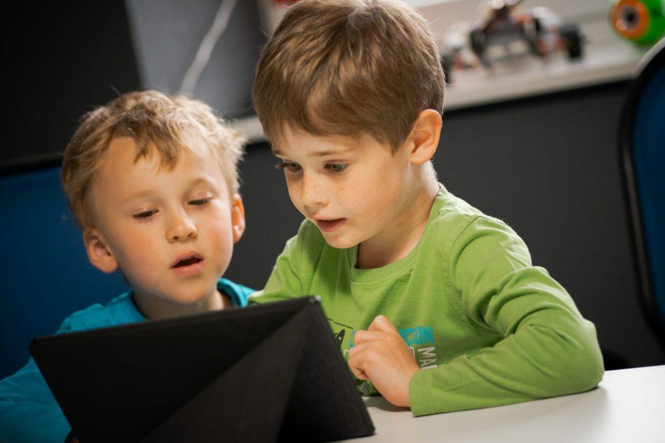 Zwei kleine Jungen programmieren auf dem Tablet