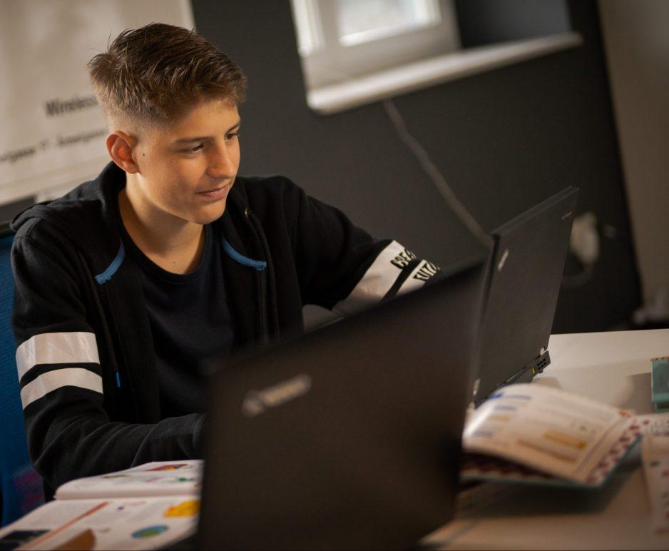 Ein Jugendliche lernt programmieren am Computer