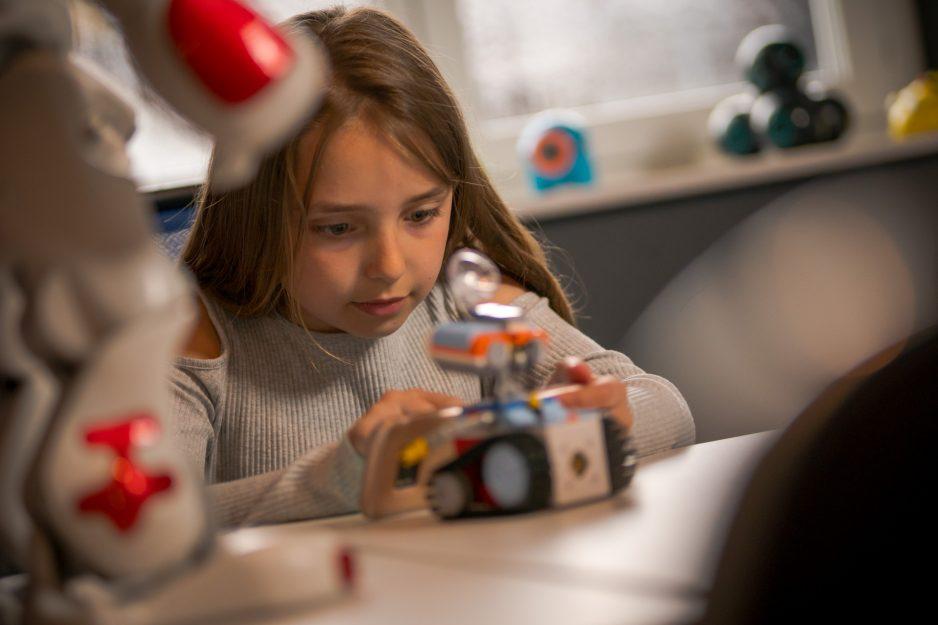Ein Mädchen programmiert einen kleinen Kinderroboter