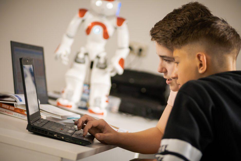Zwei Teenager programmieren einen Nao Roboter